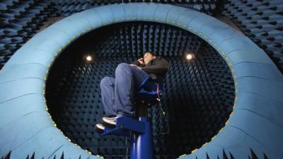 Man seated inside a really weird blue antenna test chamber, holding a phone.