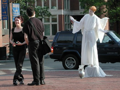 Street performer dressed as an angel poses in Harvard Square in front of two hipsters dressed in black.