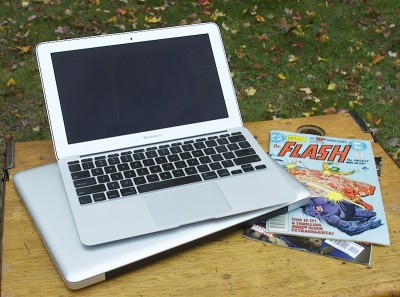 MacBook Air on top of a MacBook Pro on a table outdoors, next to comic books. The Air is the same rough size as the comics.