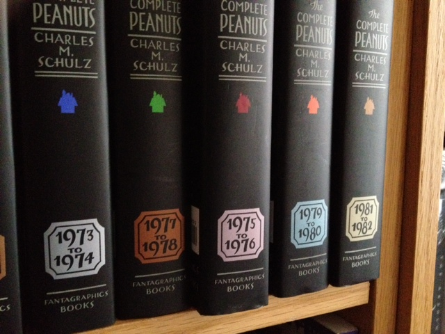"A shelf of ""Complete Peanuts"" books, with one book out of chronological sequence."